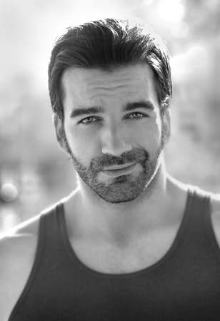 smirk: Outdoor black and white portrait of a classically good looking masculine man outdoors