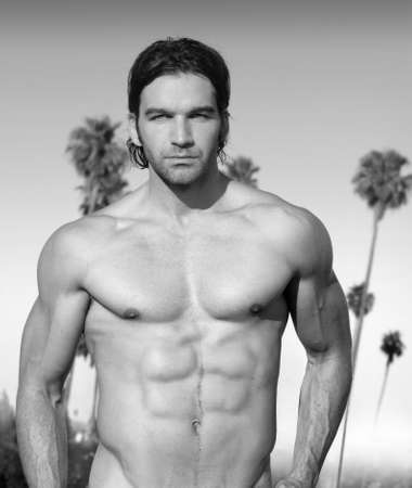 Black and white portrait of a hunky muscular shirtless male model outdoors with palm trees photo