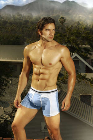 Outdoor portrait of a hunky male model turning in blue underwear with exotic location in the background photo