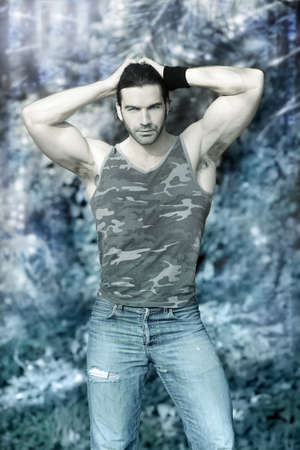 romance: Stylized outdoor portrait of muscular man posing in tank top and jeans against winter wonderland background with ice and snow Stock Photo