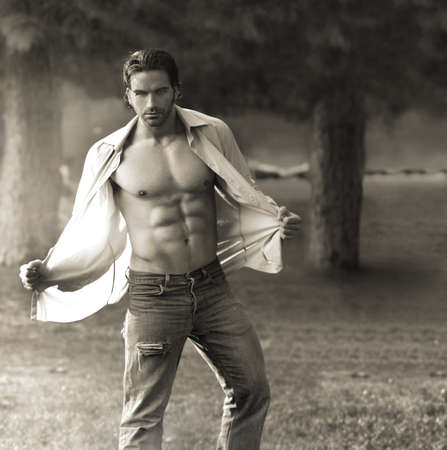 masculine: Classic portrait of muscular man outdoors opening his shirt