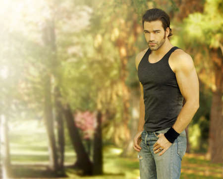 Outdoor portrait of a good looking male model in casual wear with beautiful natural background behind him