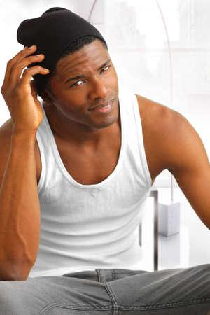 白のタンクでセクシーな男性モデルと近代的な明るい内装で黒い帽子の肖像画