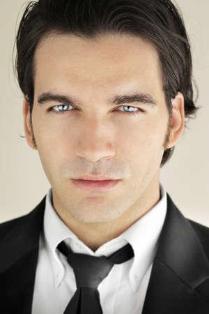 ojos azules: Detallado close-up retrato de un gran modelo de hombre en busca de traje negro y corbata con brillantes ojos azules Foto de archivo