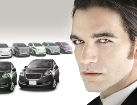 Portrait of a good looking car salesman in close up view against background of luxury bright car dealership