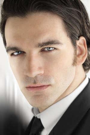 Portret van een sexy chique mannelijk model met heldere blauwe ogen in een elegante zakelijke kleding tegen een koele, moderne lichte metalen achtergrond