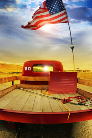 Concept photo of a vintage red vintage pick up truck with American flag waving above against rural dramatic cloudscape photo