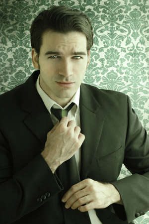 Stylized fashion portrait of a handsome male model adjusting his tie against a background of vintage wallpaper with an overall green tint