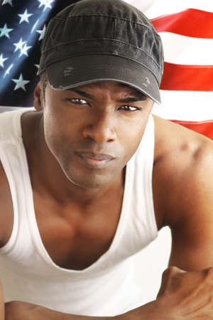 Portrait of a good looking young man against American flag backdrop photo