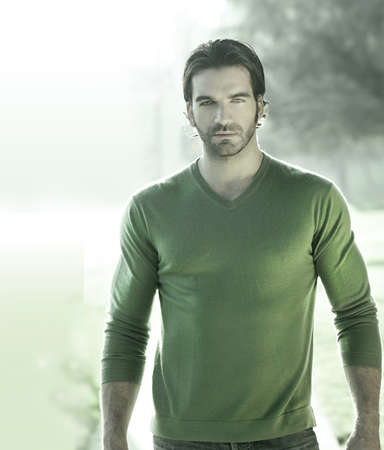 Stylized portrait of a great looking masculine guy outdoors in green sweater photo