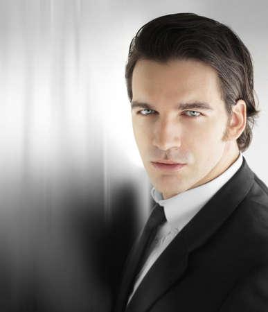 cabello negro: Retrato de un modelo dinámico hombre joven como hombre de negocios exitoso contra el fondo metálico abstracta moderna