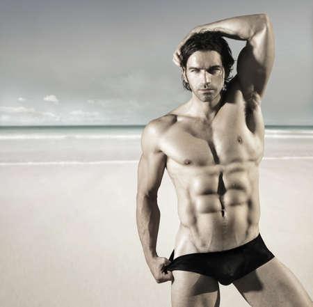 nue plage: Portrait sexy d'un mod�le de remise en forme � chaud chamois m�le tirant sur ses slips sur la plage