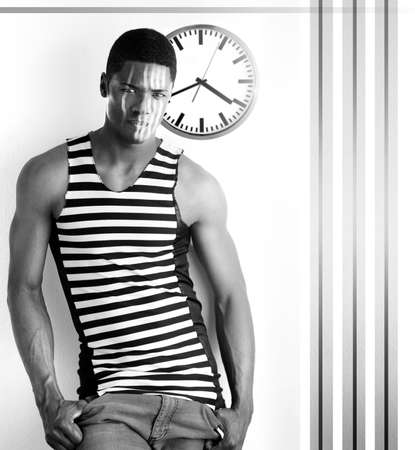 high contrast: Fine art high contrast black and white photo of a male model with abstract retro clock and stripes against white modern background
