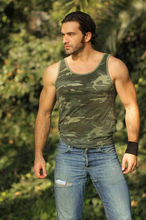 romance: Natural outdoor portrait of masculine muscular handsome male model in came tank top and ripped jeans Stock Photo