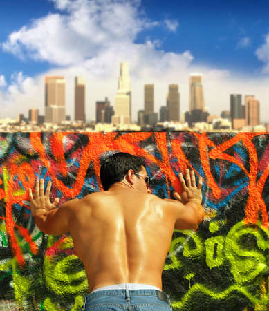 Vibrant colorful outdoor portrait of a very muscular young man leaning against graffiti covered wall with city skyline in the background taken from behind