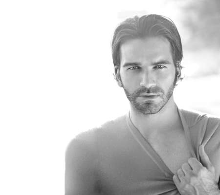 Black and white portrait of a good looking man outdoors pulling at his shirt photo