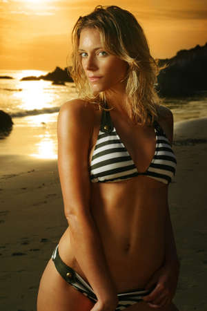 Beautiful sexy blond in bikini on the beach at sunset photo