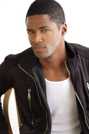 Portret van een stijlvolle leuke jonge man in leren jas tegen een witte achtergrond