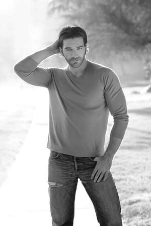 Natural black and white portrait of a classically handsome man outdoors in casual clothing photo