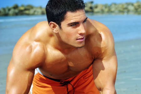 man profile: Portrait of a handsome young muscular man in swimtrunks with water ocean background