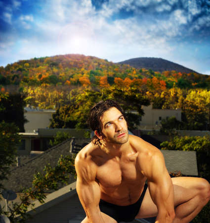 Outdoor portrait of a sexy shirtless male model crouching down against beautiful outdoor setting