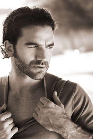 tough: Retrato de un hombre sexy al aire libre que la apertura de su camisa en tonos sepia