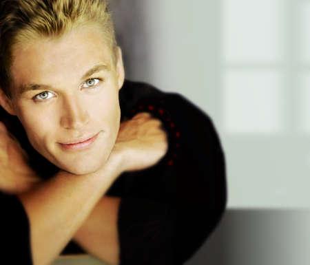 modelos hombres: Retrato de un modelo masculino guapo en pose relajada a la luz de color amarillo dorado sobre fondo moderno Foto de archivo