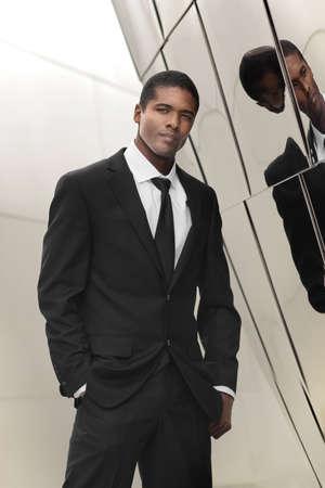 光沢のある反射壁に対する偉大な探している若い民族実業家エレガントな黒と白の肖像画のスーツします。