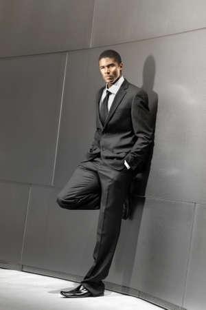 american sexy: Поразительный портрет молодой красивый успешный бизнесмен в костюме, опираясь на современные блестящие здания Фото со стока