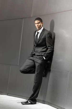 modelos negras: Sorprendente retrato de un joven hombre de negocios exitoso buena apariencia en traje apoyado en la construcción moderna y brillante Foto de archivo