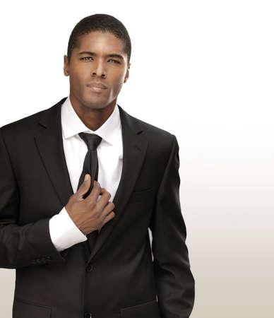 traje: Retrato de un apuesto hombre de negocios joven y guapo en traje negro con corbata contra el fondo brillante con copia espacio
