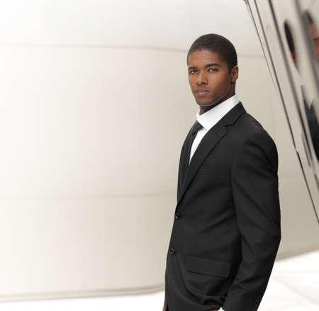 Jonge succesvolle zakenman stellen in elegante pak tegen de moderne achtergrond met kopie ruimte Stockfoto