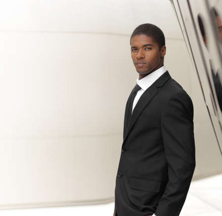 african sexy: Young successful businessman posing in elegant suit against modern background with copy space Stock Photo
