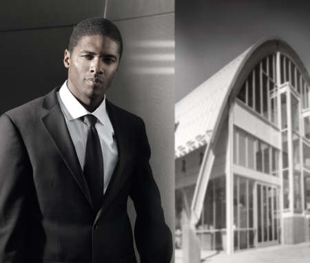 Young cool businessman in suit with dramatic lighting against modern wall with urban modern building in background