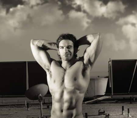 Fine art sepia toned portrait of hunky male fitness model posing against dramatic cloudscape sky photo