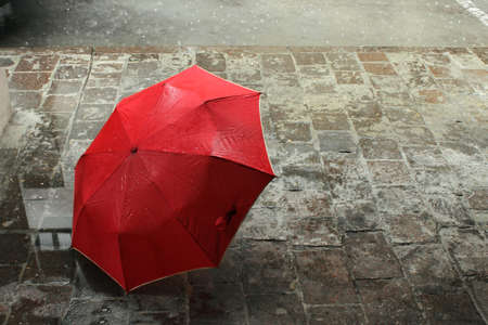umbrella rain: Bright red umbrella alone on aged european gray wet street Stock Photo