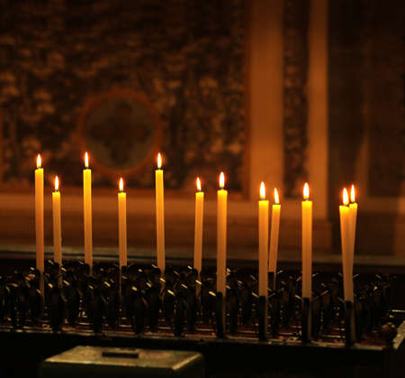 Row of tall lit candles burining in a church with dark background photo