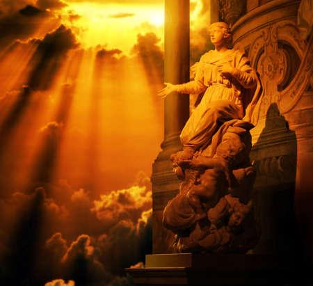 Klassieke marmeren beeld van een vrouw met de hand uitgestrekt en engeltjes aan haar voeten bad in gouden licht van boven