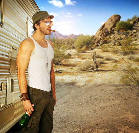 tough: Sexy portrait of a man standing outside RV holding beer in beautiful setting Stock Photo