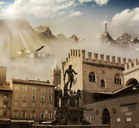 Fantastical landscape of ancient european town (Bologna, Italy) with aged buildings and statue in the foreground and dramatic mountains and sky in background