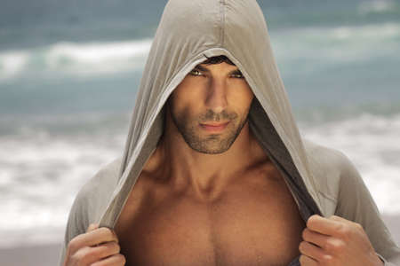 body grooming: Sexy male model outdoors wearing a hooded shirt and revealing his chest Stock Photo