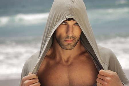 hombres sin camisa: Sexy modelo masculino al aire libre, con una camisa con capucha, revelando su pecho Foto de archivo