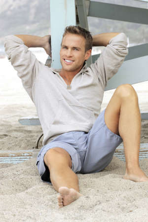 Natural outdoor portrait of great looking young man with big smile leaning in sand photo