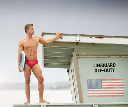 body guard: Sexy male lifeguard on top of watch tower holding body board