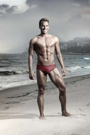 Dramatic fashion portrait of athletic fit male model on beach in bikini swimwear photo
