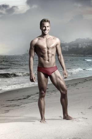 shirtless: Retrato de una manera dram�tica de la atl�tica modelo de ajuste masculina en la playa en traje de ba�o bikini