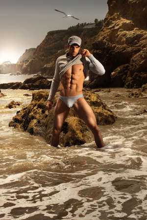 High fashion portrait of sexy male model in stunning beach setting photo