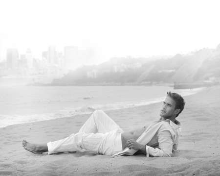 Black and white fine art portrait of a sexy young man in casual clothing lying on the beach