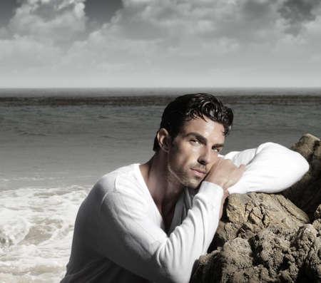 Fashion portrait of a handsome man in exotic  beautiful beach landscape Standard-Bild