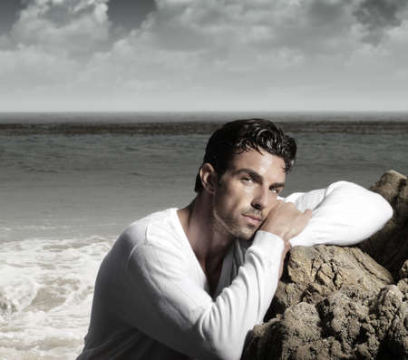 outdoor glamour: Fashion portrait of a handsome man in exotic  beautiful beach landscape Stock Photo
